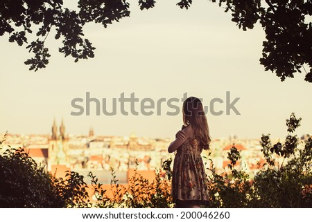 Beautiful woman looking on Prague view panorama from high hill - stock photo
