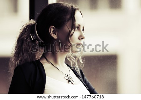 Beautiful woman looking out the window - stock photo