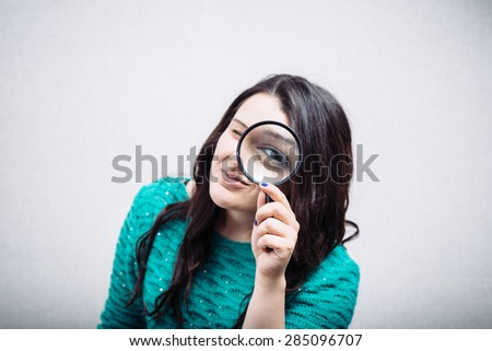 Beautiful woman looking through a magnifying glass