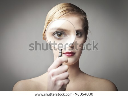Beautiful woman looking through a magnifying glass - stock photo