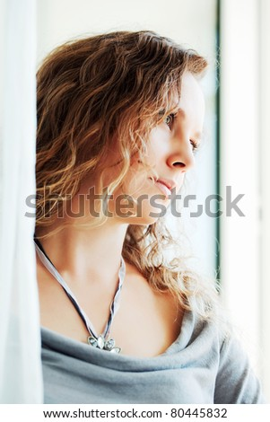 Beautiful woman looking through a window - stock photo