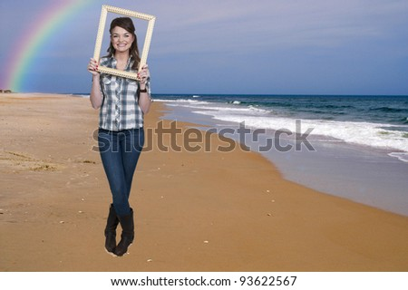 Beautiful woman looking through an ornate picture frame at the beach - stock photo