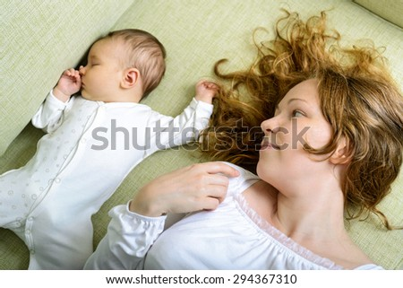 Beautiful woman looks at her newborn daughter on the couch at home - stock photo