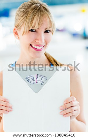 Beautiful woman loosing weight and holding a scale - stock photo
