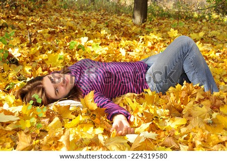 beautiful woman lying among yellow leaves - stock photo