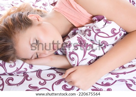 Beautiful woman lying and sleep on the snowy bed. - stock photo