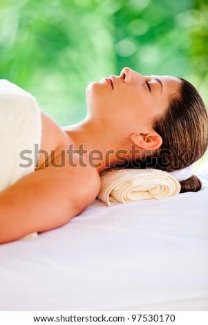 Beautiful woman lying down relaxing at a spa - stock photo