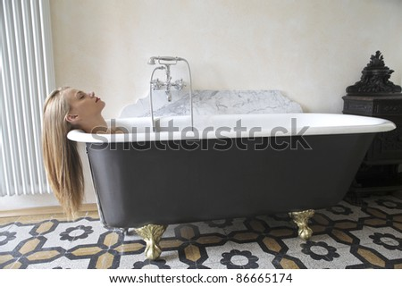 Beautiful woman lying in a bathroom - stock photo