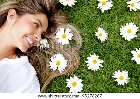 Beautiful woman lying in a garden of flowers - stock photo
