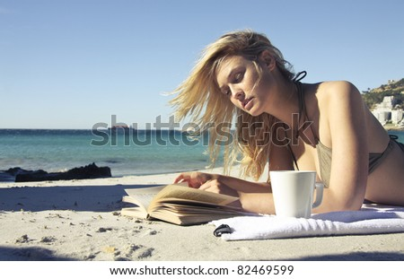 Beautiful woman lying on a beach and reading a book - stock photo