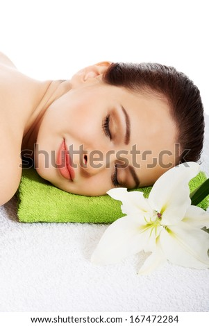 Beautiful woman lying on a towel with lily. Spa concept. Isolated on white.