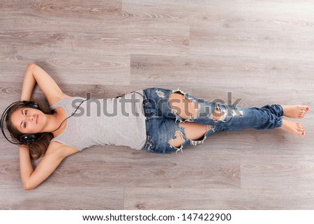 Beautiful woman lying on a wooden floor with headphones  - stock photo