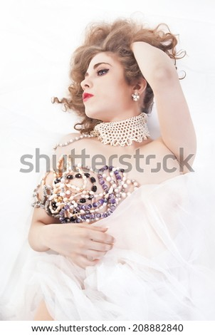 Beautiful Woman Lying On Back Covered With Jewelry And Tulle - stock photo