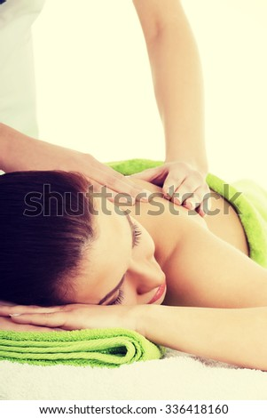Beautiful woman lying on bed in spa salon having massage. Spa concept. - stock photo