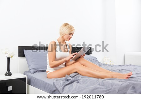 Beautiful Woman lying on bed using digital tablet, young blond girl in bedroom - stock photo