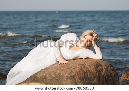 Beautiful  woman lying on the big stone at the seaside