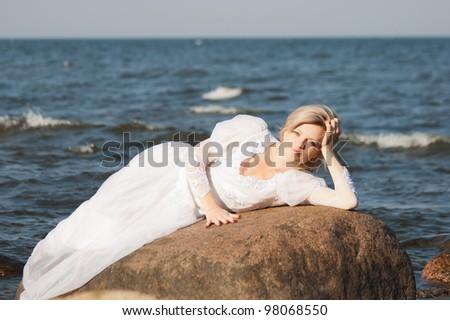 Beautiful  woman lying on the big stone at the seaside - stock photo