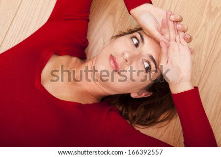 Beautiful woman lying on the floor and thinking about something