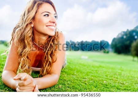 Beautiful woman lying on the floor at the park - stock photo