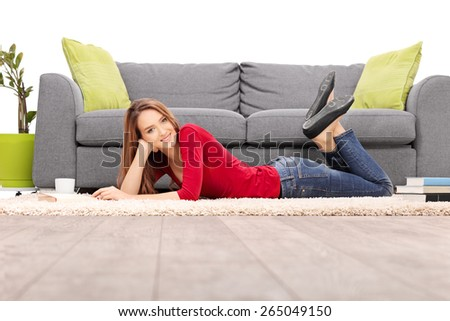 Beautiful woman lying on the floor next to a gray couch and a stack of books isolated on white background - stock photo