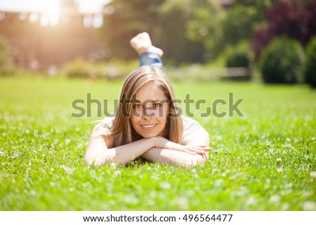 Beautiful woman lying on the grass. Lens flare effect