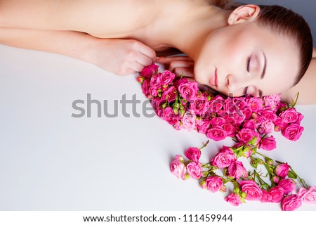 Beautiful woman lying on the rose flowers - stock photo