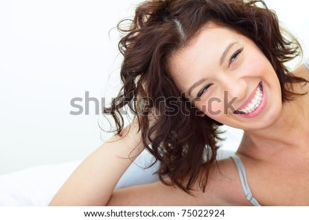 Beautiful woman lying on the sofa and laughing sincerely - stock photo