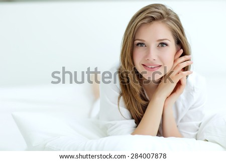 Beautiful woman lying on white bed  - stock photo