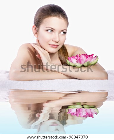 beautiful woman lying on white towel reflected in blue water - stock photo