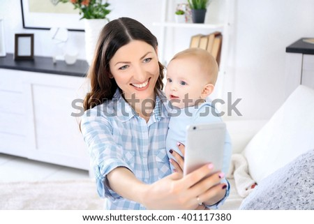 Beautiful woman make selfie on mobile phone with baby boy in room - stock photo
