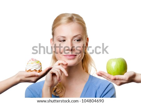 Beautiful woman makes a tough choice between cake and apple, isolated on white - stock photo