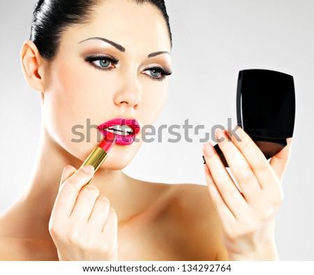 Beautiful woman makes makeup applying pink lipstick on lips. - stock photo