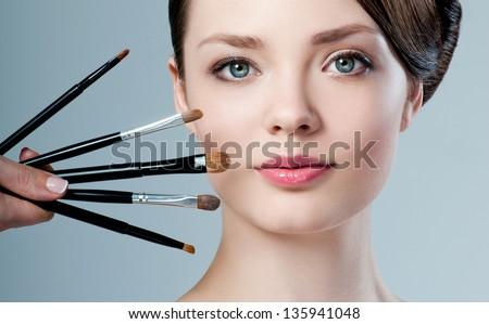 beautiful woman. Makeup brushes. - stock photo