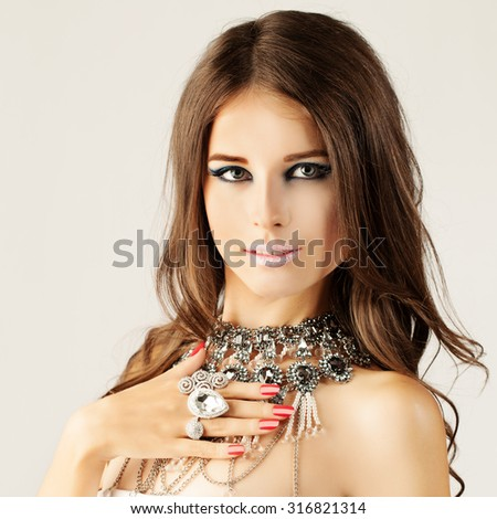 Beautiful Woman. Makeup, Red Manicure Nails and Jewelry - stock photo