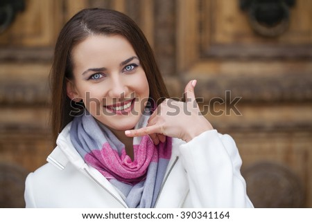 Beautiful woman making a call me gesture, outdoors in spring  - stock photo