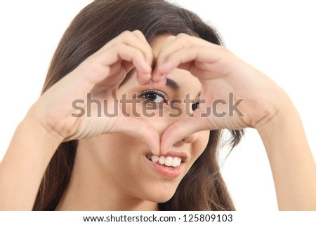 Beautiful woman making a heart shape with her hands and watching through it on a white isolated background