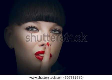 Beautiful woman making a silence gesture studio portrait dark background - stock photo