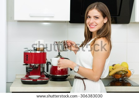 Beautiful woman making coffee for breakfast in the kitchen - stock photo