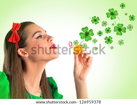Beautiful woman making four leaf clover bubbles - stock photo