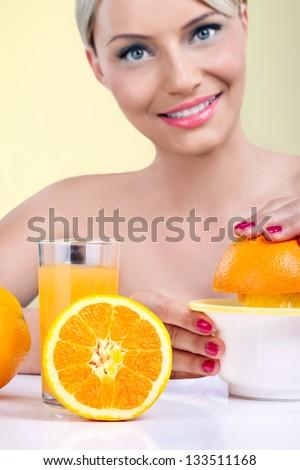 Beautiful woman making orange juice with fresh orange - stock photo