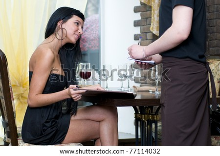 Beautiful woman making the order in restaurant - stock photo