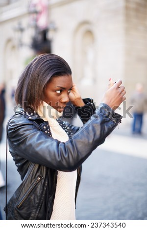 Beautiful woman making up using a smart phone as a mirror, chiming young girl looking on a mirror standing on the square - stock photo