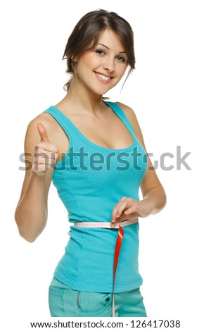 Beautiful woman measuring her waist with a measuring tape and showing thumb up, over white background - stock photo