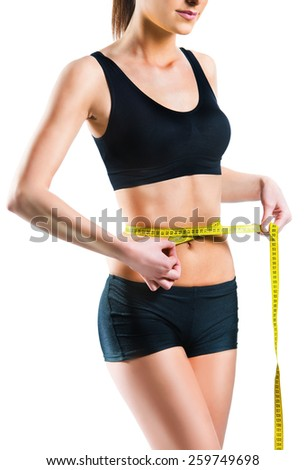 Beautiful woman measuring her waist with measuring tape - stock photo