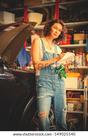 beautiful woman mechanic in blue overalls makes recording near of the car with open hood in the garage. instagram image filter retro style