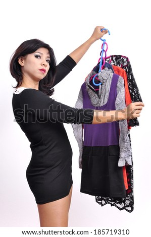 Beautiful woman mini black dress holds hangers with clothes