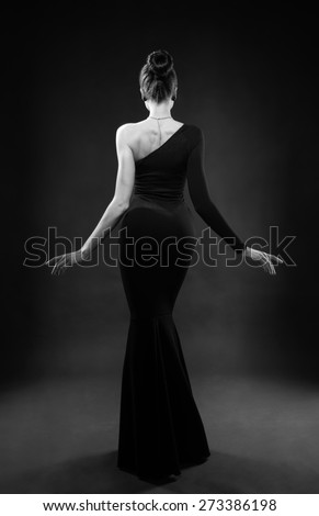 beautiful woman model posing in elegant dress in the studio, back view - stock photo
