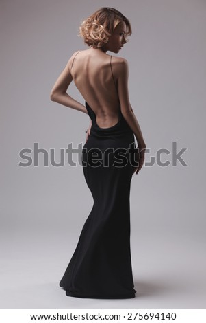 beautiful woman model posing in elegant dress on the grey studio background - stock photo