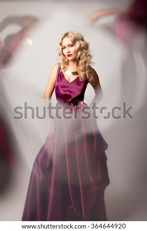 Beautiful woman model posing in elegant purple silk dress with frame of reflection in the studio - stock photo