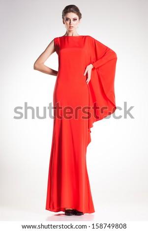 beautiful woman model posing in simple elegant red dress in the studio  - stock photo